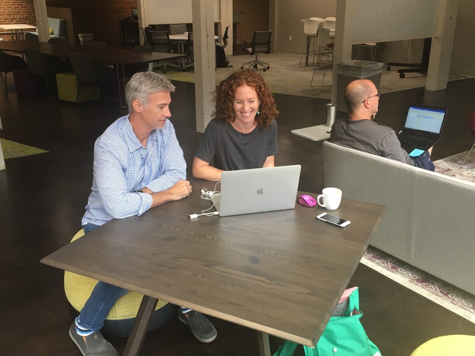 Two adults sitting at a table working on a laptop