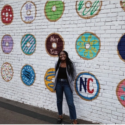 Crystal Sefah poses in front of a painted brick wall