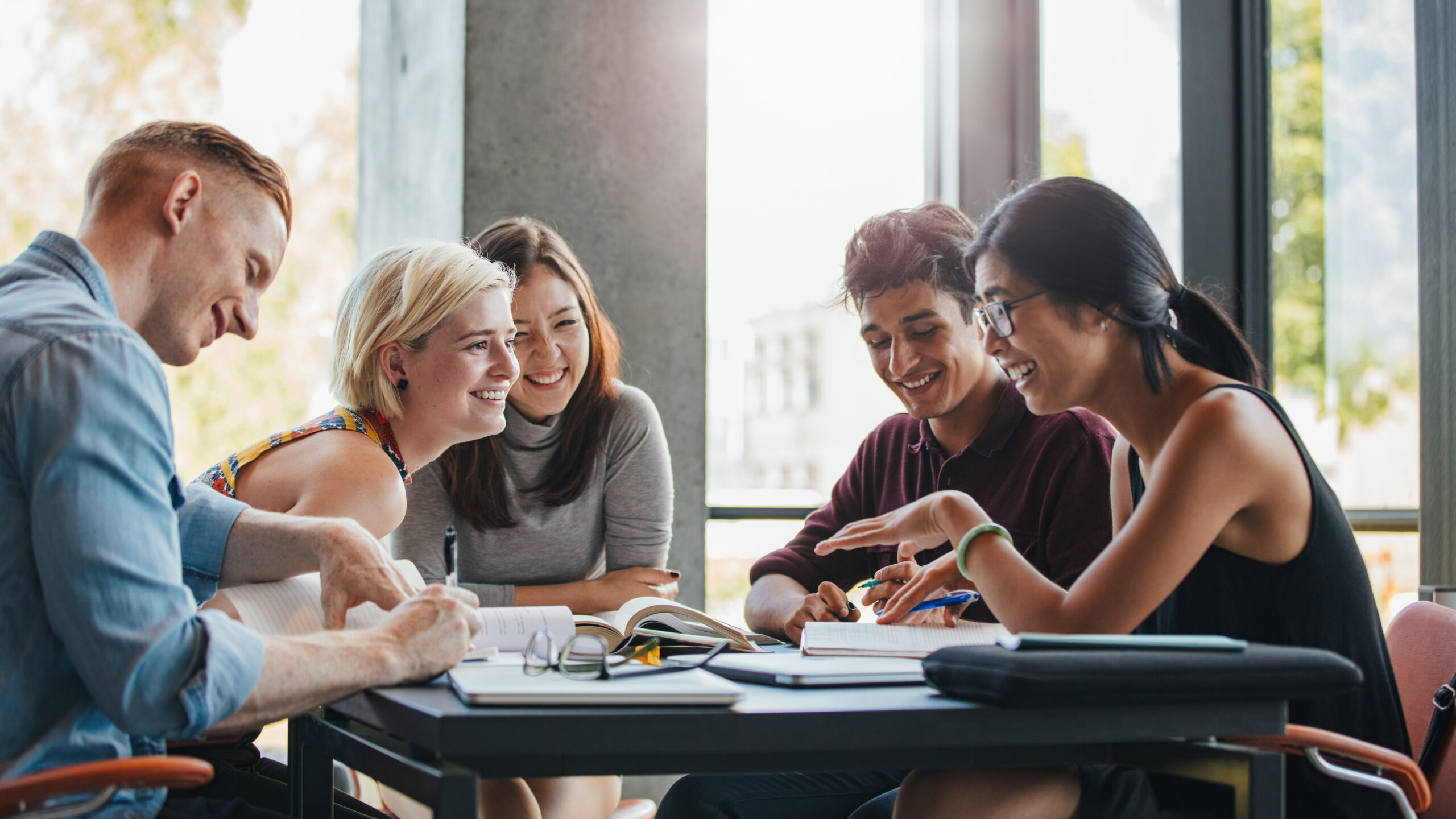 5 young adults around table collaborating